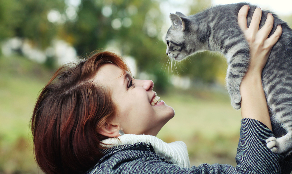 a woman holding her cat in the air